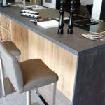 Küche in Spachtelbeton Graphit mit Alteiche natur, Inselrückseite in Alteiche natur zum sitzen mit Regalen